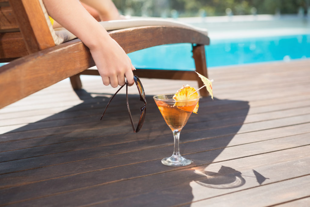 Women at the pool drinking a cocktail