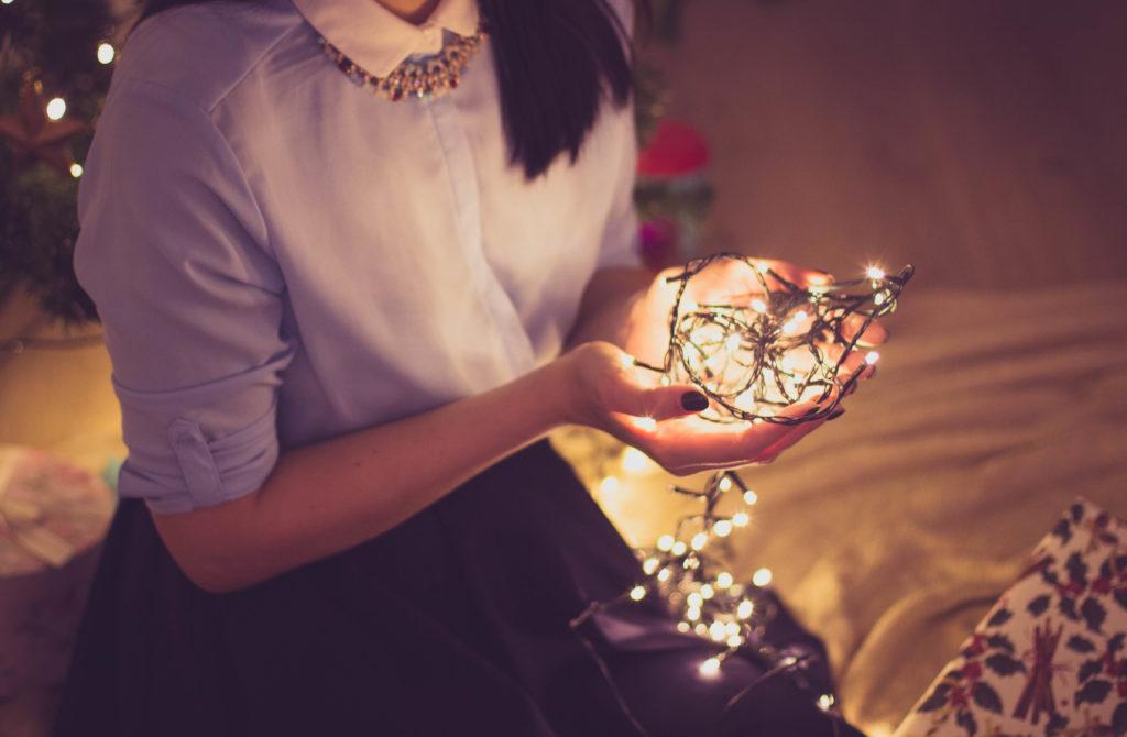 Girl holding string of lights